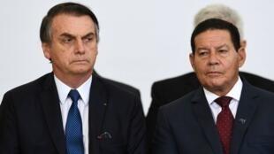 El presidente brasileño Jair Bolsonaro y su vicepresidente Hamilton Mourão asisten a una ceremonia que marca los primeros 100 días de su gobierno en el Palacio de Planalto en Brasilia, el 11 de abril de 2019.