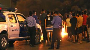 أفراد أمن عراقيون يراقبون متظاهرين يحرقون إطارات خلال احتجاج ضد البطالة وارتفاع تكاليف المعيشة في البصرة 12 تموز/يوليو 2018