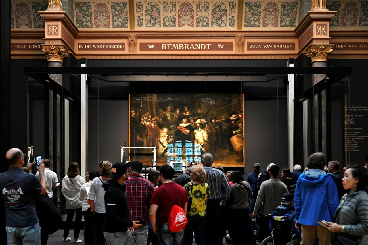 Asistentes del Rijksmuseum en Amsterdam observan el inicio del trabajo de restauración de 'La ronda de noche', Países Bajos.  8 de julio de 2018.