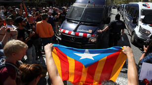 Un manifestante sostiene una Estelada (bandera separatista catalana) en frente de una camioneta de la policía regional en las afueras del edificio del ministerio de Economía catalán durante una serie de allanamientos de la policía española en oficinas de gobierno, en Barcelona, el 20 de septiembre de 2017.