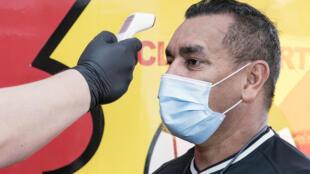 Un empleado le toma la temperatura al DT del  Sport Herediano, el argentino José Giacone, antes de una práctica de ese equipo costarricense de fútbol en Heredia, Costa Rica, el 4 de mayo de 2020