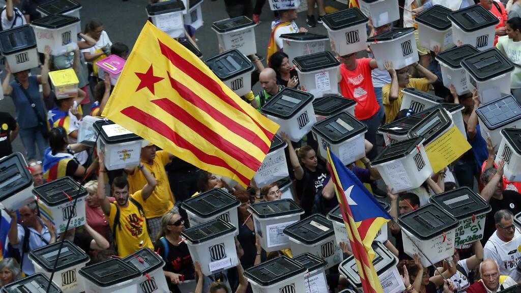Manifestantes sostienen urnas el 1 de octubre de 2018, durante la manifestación que conmemoró un año desde la celebración del referendo de independencia