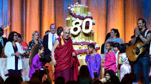 The Dalai Lama blows a lone candle on his birthday cake at the Honda Center on July 5, 2015 in Anaheim, California, as the Tibetan Buddhist religious leader celebrated his 80th birthday.