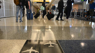 Des passagers portant des masques avant d'embarquer à l'aéroport George Bush Intercontinental à Houston, au Texas, le 6 mai 2020