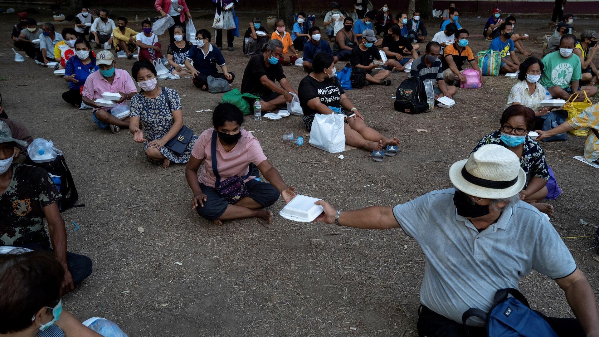 أشخاص متضررون من إجراءات الحجر الصحي في تايلاند يتلقون وجبات مجانية في بانكوك، 21 أبريل/نيسان 2020.