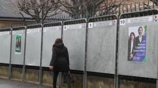 Una pasante frente a panales electorales el 2 de marzo de 2020 en París.