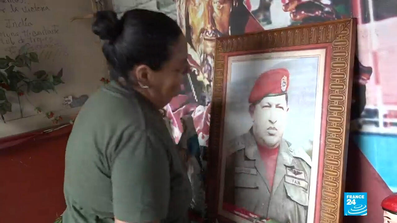 Une habitante du quartier se recueille devant la photo de l'ancien président Hugo Chavez.