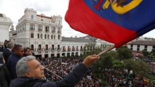 El presidente Lenín Moreno ondeando una bandera de Ecuador en el balcón del Palacio de Carondelet en Quito.