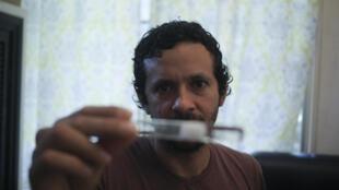 El investigador panameño Dumas Gálvez muestra un tubo de ensayo con hormigas en su casa de Ciudad de Panamá, el 12 de mayo de 2020