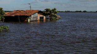 Una casa se ve parcialmente sumergida en una calle inundada después de las fuertes lluvias que causaron el desbordamiento del río Paraguay, en un vecindario en las afueras de Asunción, capital de Paraguay, el 25 de mayo de 2019.