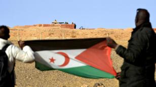 Des Sahraouis brandissent le drapeau du Front Polisario, près d'un poste militaire marocain, dans la région de Mahbes.