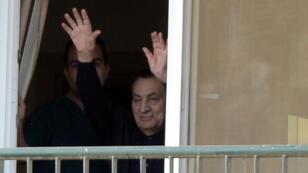 Hosni Moubarak salue ses partisans depuis la fenêtre de sa chambre de l'hôpital militaire du Caire le 4 mai.