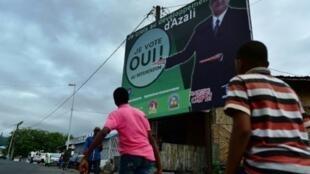 """مارة أمام لافتة تدعو إلى التصويت بـ""""نعم"""" في الاستفتاء الدستوري وتُظهر الرئيس غزال عثمان في 27 تموز/يوليو 2018 في موروني في جزر القمر"""