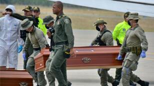 Personal de la Policía de Colombia en Cali cargan los ataúdes con los cuerpos hallados en una zona selvática en el suroeste del país. 22 de junio de 2018.
