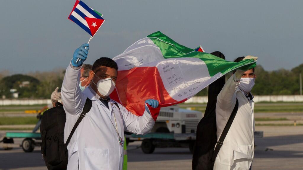 Los médicos de la brigada médica cubana del contingente Henry Reeve llevan una bandera italiana a su llegada de Lombardía, Italia. En La Habana, Cuba 8 de junio de 2020.