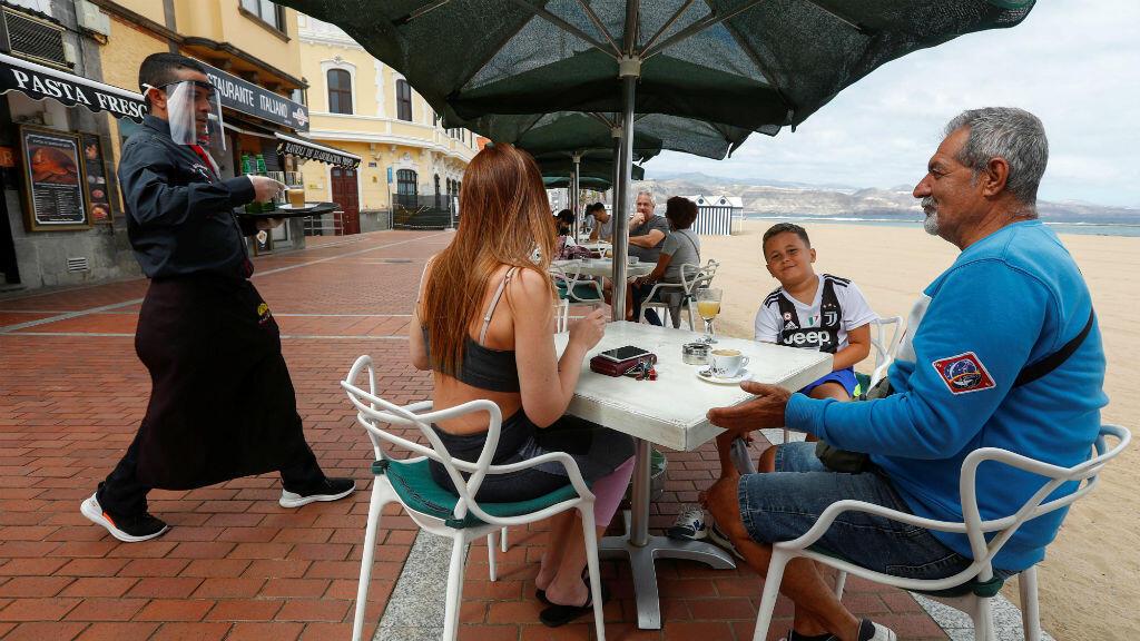 Un mesero atiende a varios clientes en el paseo marítimo de la playa de Las Canteras durante la reapertura en algunas provincias españolas durante la fase 1, en medio del brote de la enfermedad del coronavirus Covid-19 en la isla de Gran Canaria, España, el 11 de mayo de 2020.