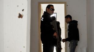 Des policiers tunisiens pénètrent dans une maison dans laquelle des jihadistes ont été tués au cours d'une opération policière le 11 mai 2016, dans la ville de Mnihla, dans la région de l'Ariana.