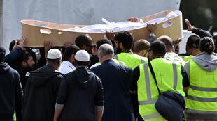 Plusieurs personnes portent le cercueil d'une victime de l'attentat de Christchurch lors de funérailles, le 20 mars 2019, au cimetière Memorial Park de Christchurch.