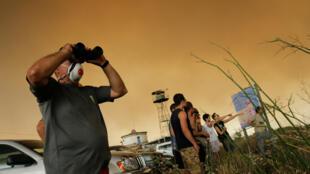 Des habitants observent l'incendie près du village catalan de Maials, le 27juin2019.