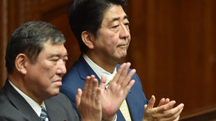 Japan's Prime Minister Shinzo Abe (R) and Regional Revitalization Minister Shigeru Ishiba (L) applaud the passing of controversial security bills during a lower house parliamentary session on July 16, 2015.
