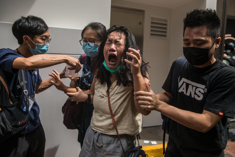 Una mujer reacciona después de ser golpeada por un gas pimienta lanzado por la policía durante las protestas en Hong Kong contra la ley de seguridad nacional.