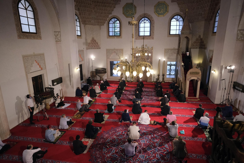 Des fidèles portant des masques enchaînent les prières de l'Aïd al-Adha tout en maintenant une distance sociale à la mosquée Gazi Husrev-beg à Sarajevo, en Bosnie, le vendredi 31 juillet 2020.