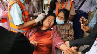 متظاهرة تتلقى الرعاية الصحية بعد إصابتها بطلقات قوات الأمن في ماندالاي في بورما في 20 شباط/فبراير 2021