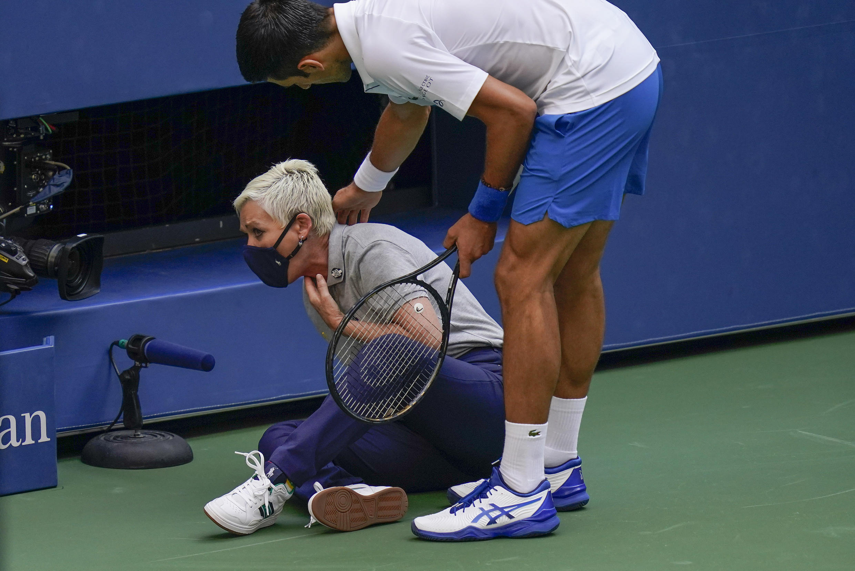 Novak Djokovic se rend auprès de la juge de touche après l'avoir heurtée avec une balle en réaction à la perte d'un point contre Pablo Carreno Busta, lors du quatrième tour des championnats de tennis de l'US Open, dimanche 6 septembre  2020, à New York.