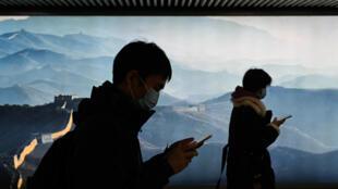 Un homme et une femme portant un masque consultent leur téléphone dans le métro à Pékin le 11 mars 2020