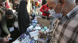 بائع عراقي يعرض على زبائنه كمامات وسوائل تعقيم في أحد شوارع بغداد في الرابع من كانون الأول/ديسمبر 2020