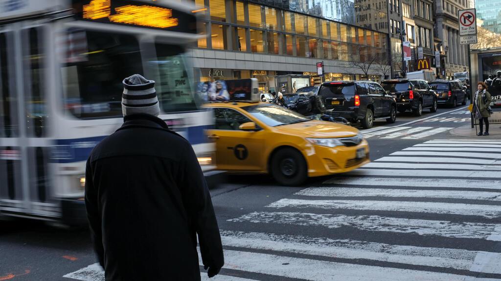 Un peatón espera para cruzar la calle mientras el tráfico se mueve a través de Midtown Manhattan, el 25 de enero de 2018 en la ciudad de Nueva York.