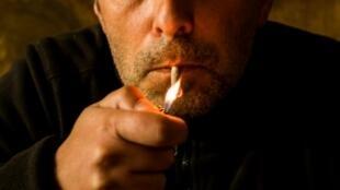 Un client du bar Booze Cooperativa allume une cigarette à Athènes le 7 mai 2019