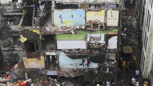 Rescue workers search for survivors in the rubble of a collapsed building in Bhiwandi, near Mumbai
