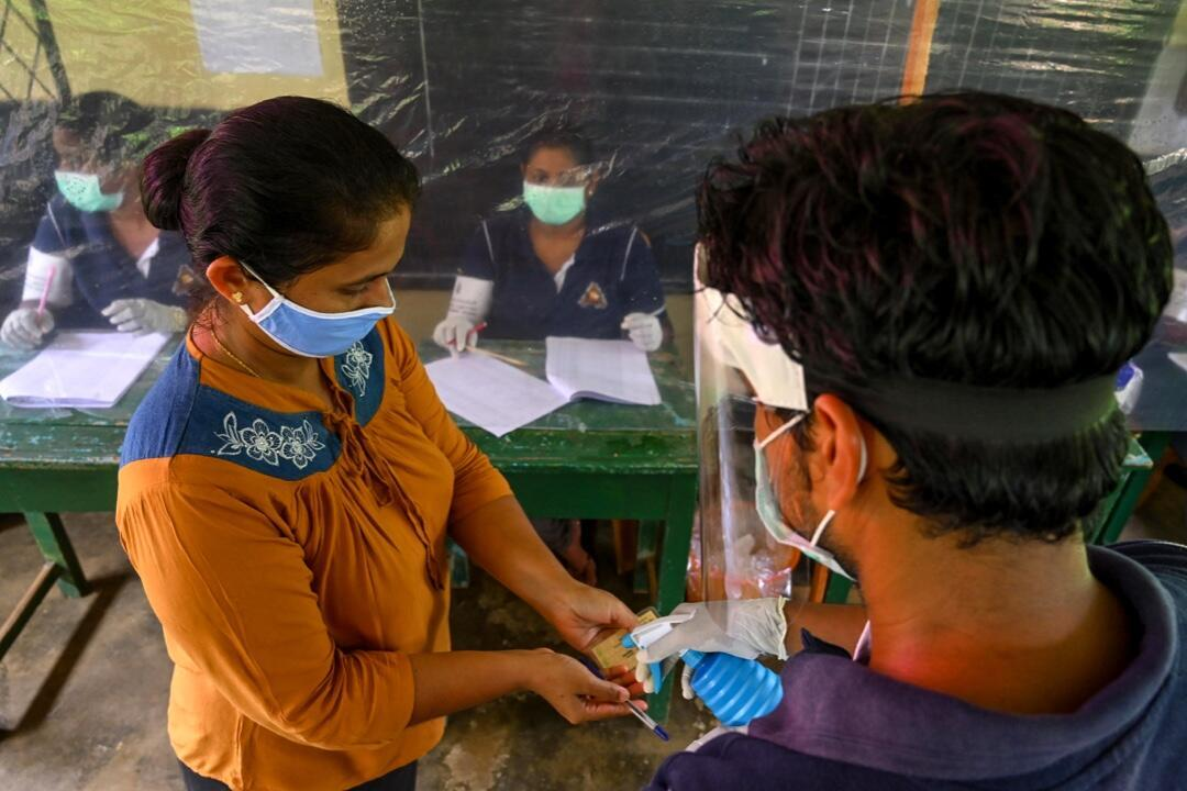 Un funcionario rocía desinfectante el 14 de junio de 2020 sobre las manos de una votante durante la simulación para probar las pautas contra el Covid-19 que serán implementadas en Sri Lanka en las elecciones del 5 de agosto.