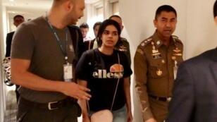 رهف القنون رفقة سلطات الهجرة التايلاندية في مطار بانكوك، 7 كانون الثاني/يناير 2019