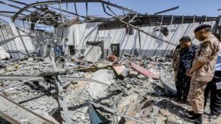 Des militaires du Gouvernement d'union nationale(GNA) inspectent des décombres après le raid sur un camp de détention de migrants, le 3juillet2019, près de Tripoli.