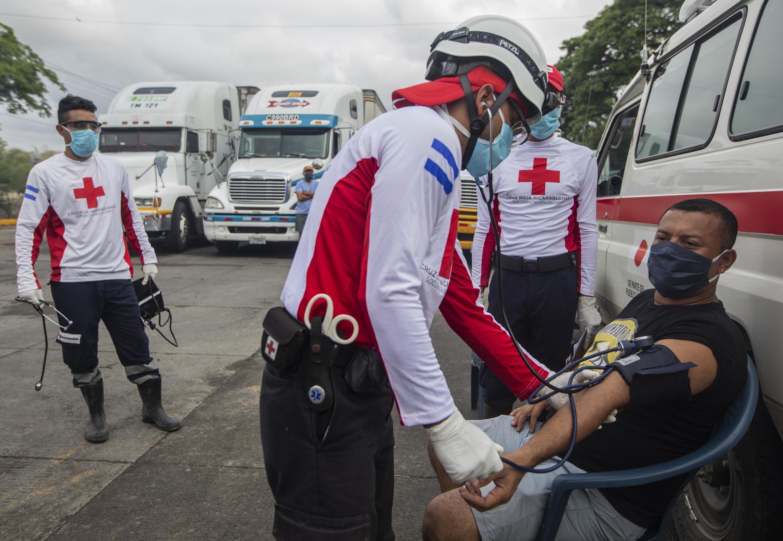 Trabajadores de la Cruz Roja Internacional controlan la presión y la temperatura de los camioneros durante un bloqueo en la frontera de Peñas Blancas entre Nicaragua y Costa Rica, en Rivas, Nicaragua, el 28 de mayo de 2020.