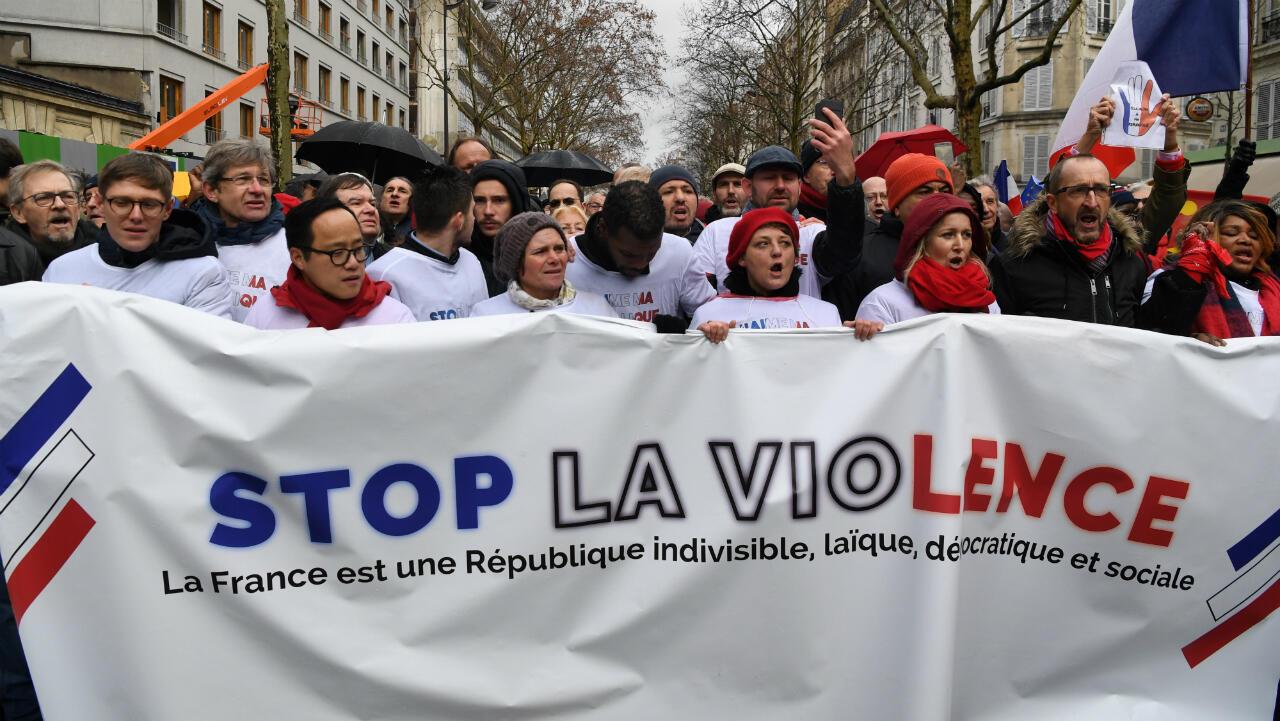 Manifestantes sostienen un cartel durante un mitin de 'Pañuelos Rojos', contra los 'Chalecos Amarillos'