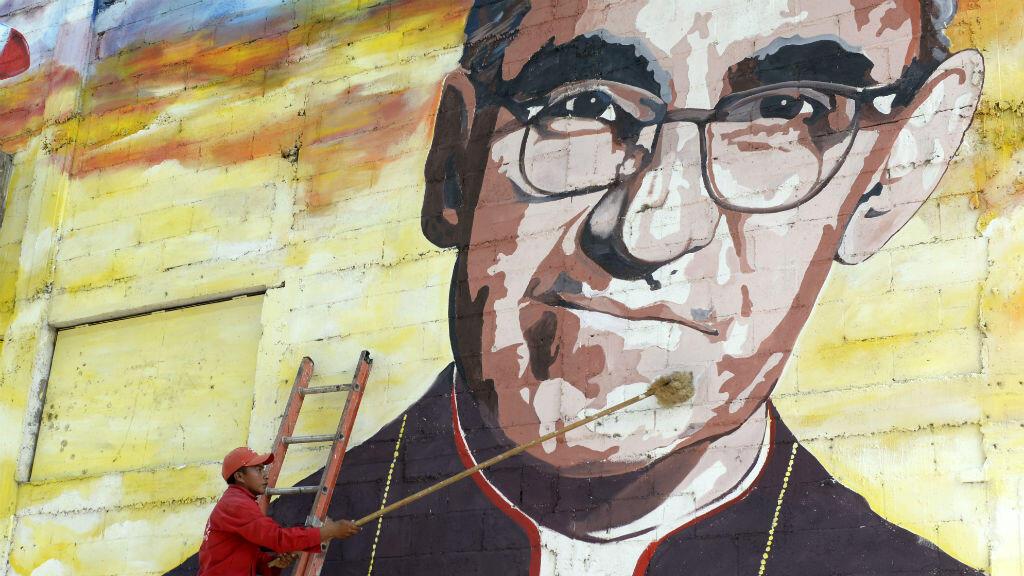 Un homme nettoie une fresque murale représentant Oscar Romero, le 19 mai 2015 à Panchimalco, près de San Salvador.