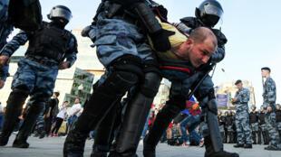 Des policiers anti-émeute arrêtent un manifestant lors d'un rassemblement non autorisé sur la place Trubnaya à Moscou, le 27 juillet 2019.