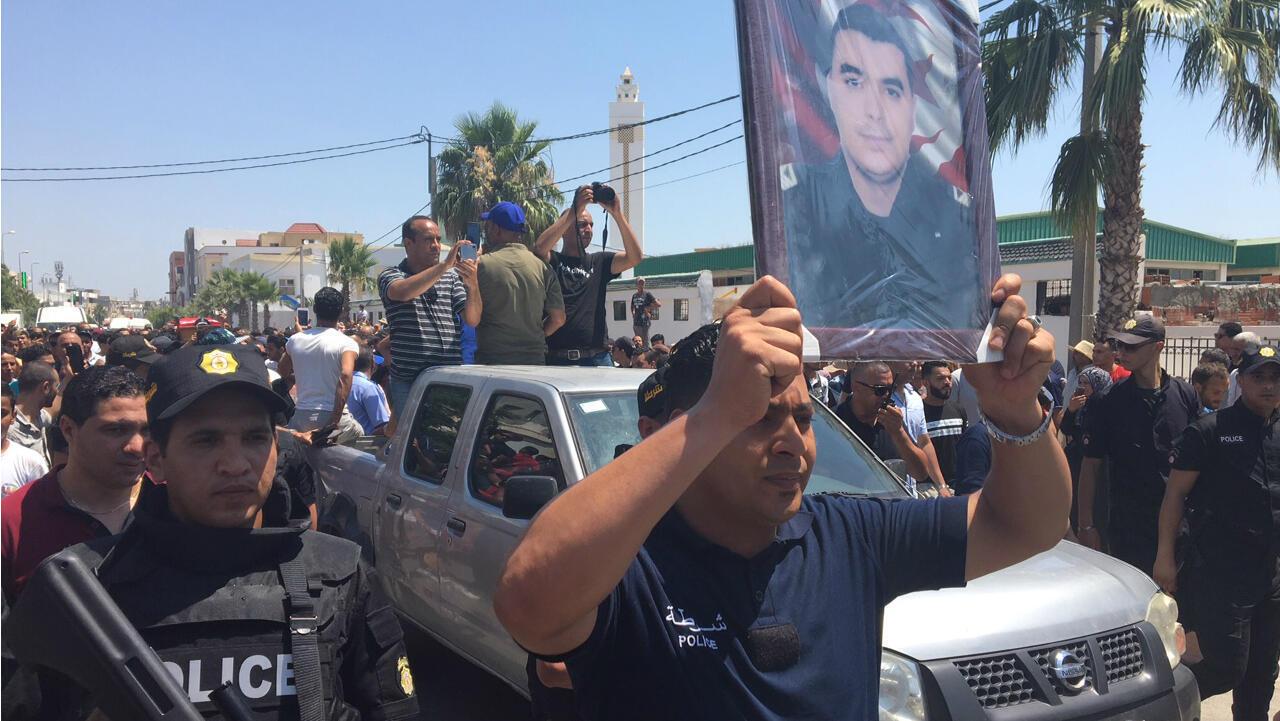 Un policier portant le portrait de Mehdi Zammali, tué pendant les attentats de Tunis, lors de son enterrement le 28 juin 2019 à la capitale tunisienne.