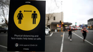 People jog past a social distancing sign on the first day of New Zealand's new coronavirus disease (COVID-19) safety measure that mandates wearing of a mask on public transport, in Auckland, New Zealand, in this August 31, 2020, file photo.