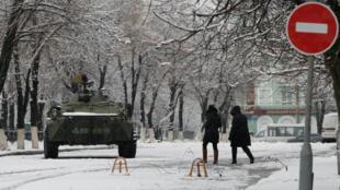 Mujeres pasan al frente de un tanque en el centro de la ciudad de Luhansk, controlada por los rebeldes separatistas, en Ucrania, el 22 de noviembre.