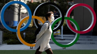 A woman wearing a protective face mask, following an outbreak of the coronavirus disease (COVID-19), walks past the Olympic rings in front of the Japan Olympics Museum in Tokyo, Japan March 13, 2020.