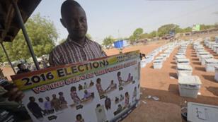 Un membre de la commission électorale pose devant des urnes préparées, tenant une affiche qui sera exposée dans chaque bureau de vote.