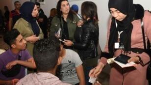 عاملون مع الهيئة العليا المستقلة للانتخابات في تونس يتجولون في شوارع تونس العاصمة لاقناع الشبان خاصة بتسجيل اسمائهم استعدادا للانتخابات العامة في نهاية العام الحالي