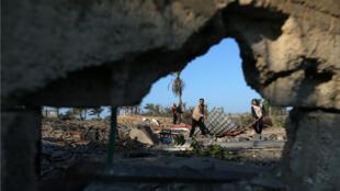 Los palestinos inspeccionan un sitio que pertenece a Hamás después de que fuera atacado por aviones de combate israelíes en el sur de la Franja de Gaza el 2 de noviembre de 2019.