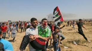فلسطيني جريح ينقله زميل له بعد إصابته خلال صدامات قرب السياج الحدودي شرق غزة في 15 أيار/مايو 2019