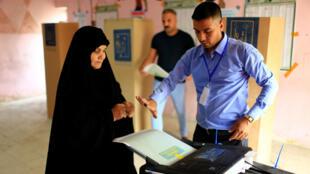 Una mujer iraquí da su voto en un colegio electoral durante las elecciones parlamentarias en Bagdad, el 12 de mayo de 2018.