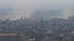 De la fumée s'élève dans le ciel depuis la ville syrienne de Ras al-Aïn, le 18 octobre 2019, à proximité de la frontière turque.